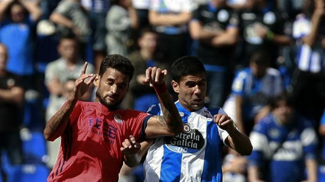 El lateral del Deportivo de La Coruña Juanfran salta con el delantero de la Real Sociedad William José (Foto: EFE)