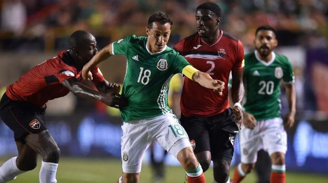 El jugador de Trinidad y Tobago Moses agarra al capitán de México, Andrés Guardado (Foto: AFP)