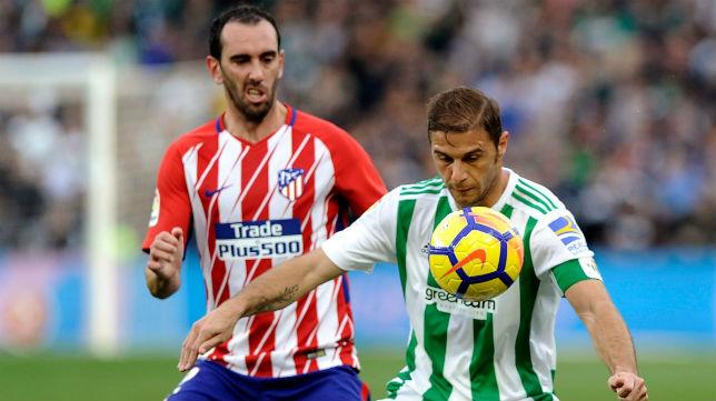 Joaquín controla un balón ante Godín en el Betis-Atlético