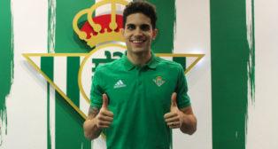 Marc Bartra posa sonriente ante el escudo del Real Betis tras la firma de su contrato (Foto: RBB)