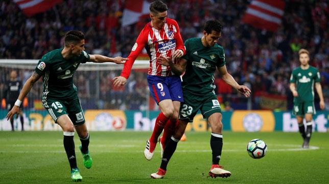 Mandi le arrebata el balón a Fernando Torres ante Bartra en el Atlético de Madri- Betis (Foto: Reuters).