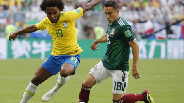Guardado disputa un balón con el jugador de Brasil Willian (Foto: EFE)