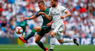 Lo Celso controla ante la oposición de Nacho, durante el partido en el Bernabéu (Foto: EFE)