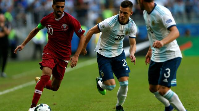 Hassan Al-Haydos conduce el balón ante Lo Celso en el Catar-Argentina de la Copa América