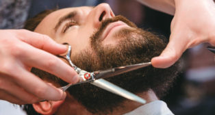 Hairdresser doing haircut of beard using comb and scissors to young attractive man in men's hair salon