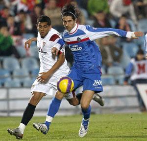 Sevilla FC: Alves pugna con De la Red un balón durante el partido