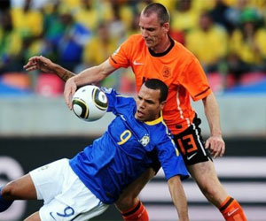 Sevilla FC: Luis Fabiano intenta controlar un balón de espaldas a un defensor holandés
