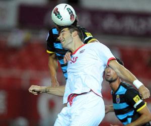Sevilla FC: Negredo salta por un balón en un partido de esta pretemporada