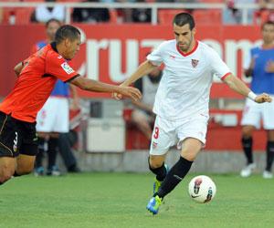 Negredo conduce el balón ante un defensa del Valencia