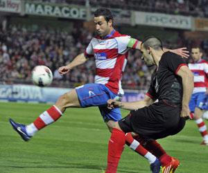 Negredo centra un balón ante la oposición de un rival