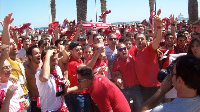 Aficionados sevillistas cantan en la Playa de la Malvarrosa de Valencia