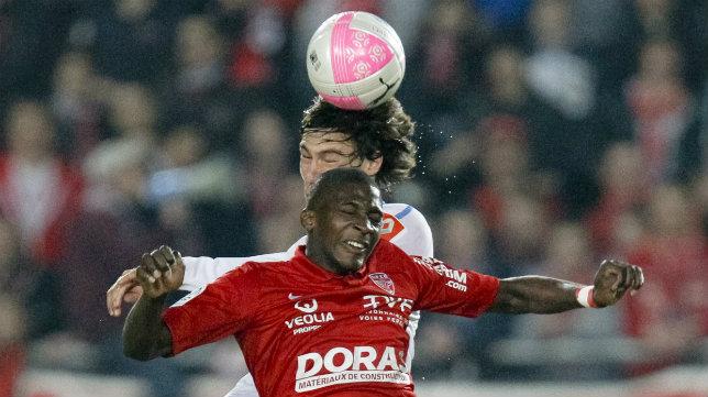 Stambouli, detrás, salta por un balón con un rival