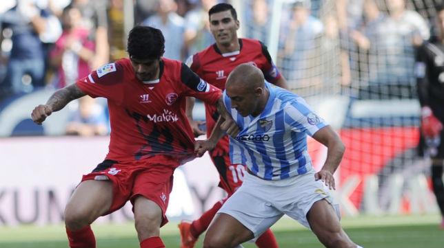 Banega y Reyes ante Amrabat, en el Málaga-Sevilla de la temporada 2014-15