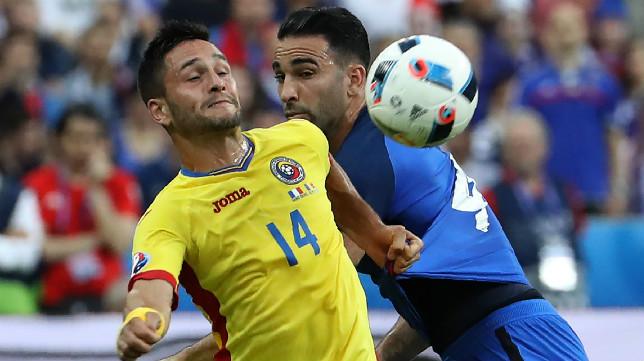 Florin Andone disputa un balón con Rami durante el Francia-Rumanía de este viernes