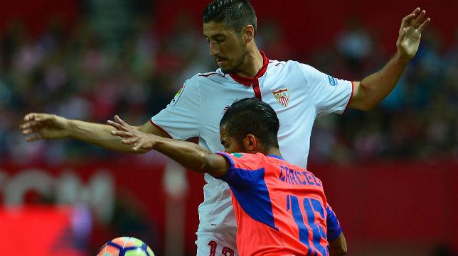 Escudero trata de controla ante la presión del futbolista del Granada Carcela (Foto: AFP)
