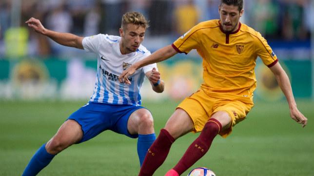 Escudero conduce un balón ante la presencia de Ontiveros en el Málaga-Sevilla