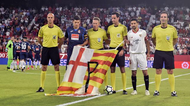 Los capitanes del Sevilla y el Espanyol junto al trío arbitral portando la bandera en homenaje a las víctimas (foto: EFE/Raúl Caro)