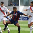 Álex Muñoz y Berrocal, defensas del Sevilla Atlético, luchan por un balón con el delantero del Huesca. Foto: LaLiga
