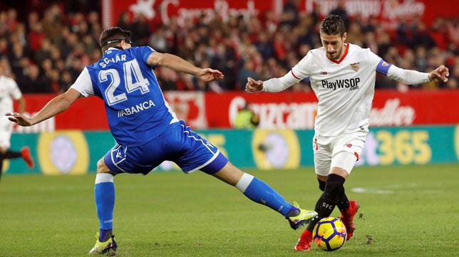 El lateral del Sevilla, Escudero trata de superar al jugador del Deportivo Fabian Lukas Schär (EFE/Julo Muñoz)