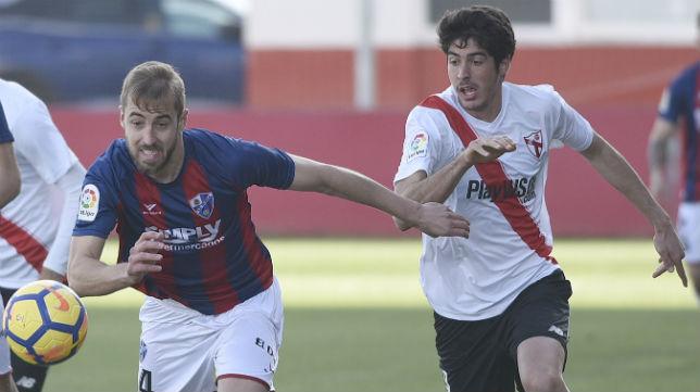 Carlos Fernández, delantero del Sevilla Atlético, pugna un balón con un futbolista del Huesca (Foto: J. Spínola)