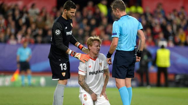 David Soria asiste a Kjaer tras una acción en el Sevilla-Bayern