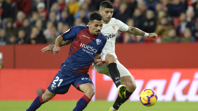 Banega pugna un balón con Gürler en el Huesca-Sevilla (AFP)