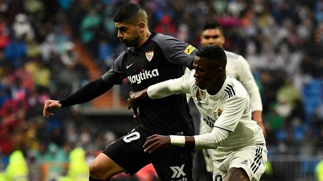 Banega pugna con Vinicius durante el Madrid-Sevilla (Foto: AFP)