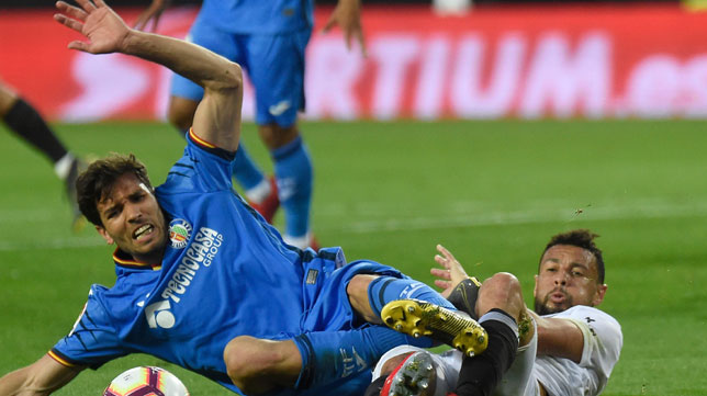 Cabrera y Coquelin pugnan por un balón durante el Valencia - Getafe (Foto: AFP)