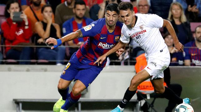 Reguilón (posible titular en el Sevilla - Levante) disputa el balón con Luis Suárez en el Barcelona-Sevilla (EFE)