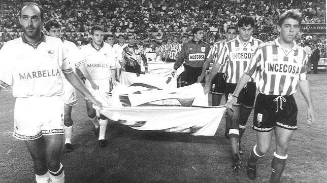Rafa Paz y Cañas, capitanes del Sevilla y del Betis, portan la pancarta en apoyo a Ian Reina antes del derbi de octubre de 1994 (Foto: ABC).