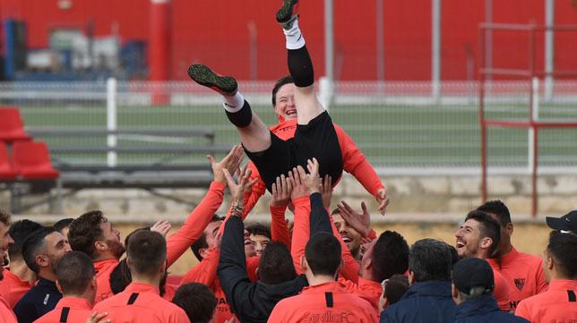 Los jugadores del Sevilla mantean a uno de los jugadores del equipo de la liga Genuine (J. J. Úbeda)