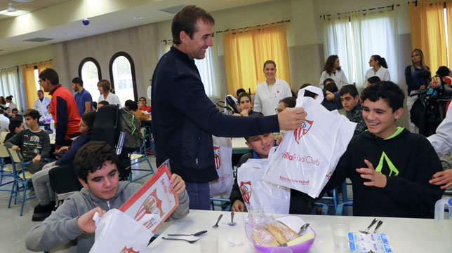 El técnico del Sevilla FC, Julen Lopetegui, entrega una bolsa de regalos a uno de los niños de San Juan de Dios (Rocío Ruz)