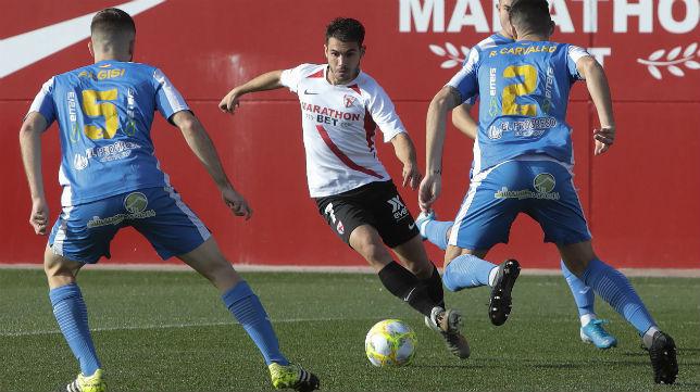 Lara, del Sevilla Atlético, encara a dos futbolistas del Villarrubia (Foto: Raúl Doblado)