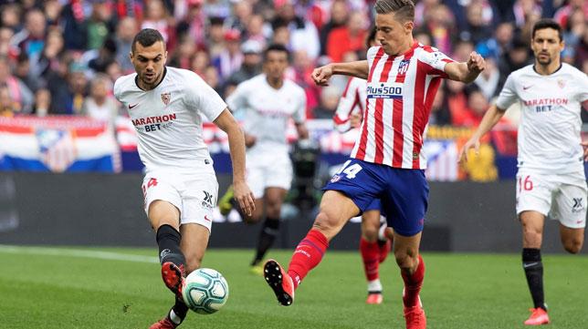 Joan Jordán da un pase ante Marcos Llorente durante el Atlético-Sevilla de LaLiga Santander (Foto: EFE).