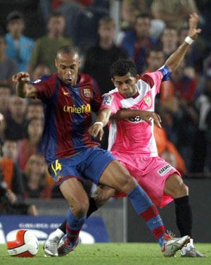 Sevilla FC: Alves y Henry disputan un balón en el partido de Liga