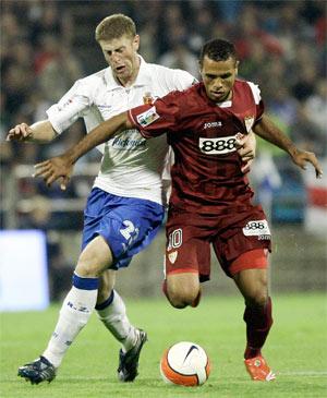 Sevilla FC: Luis Fabiano se lleva el balón ante la presión de Sergio en el partido de la primera vuelta