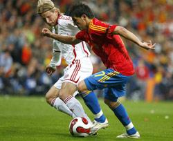 Poulsen pugna por un balón con Villa en la fase clasificatoria de la Eurocopa 2008