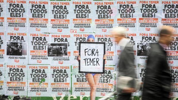 Una persona pasa frente a un muro lleno de carteles en contra del presidente de Brasil, Michel Temer