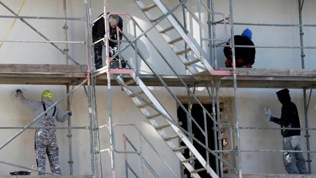 Obreros pintan la fachada de un edificio en Berlín