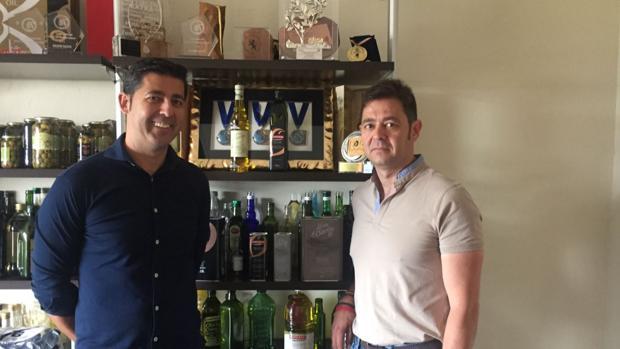 José Manuel Muela y su hermano Mateo, ante un expositor con sus premiados aceites de oliva virgen extra