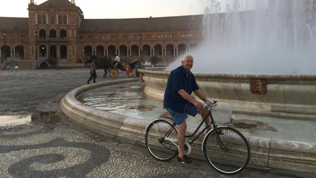 Isaías Parrilla sigue pedaleando a sus casi 80 años. En la imagen, junto a la fuente de la Plaza de España de Sevilla