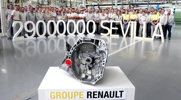 La caja de velocidad número 29 millones en primer plano con la plantilla de la factoría de Sevilla detrás