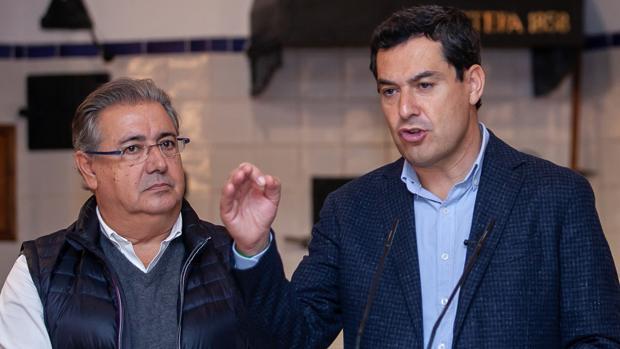 El candidato número uno del PP por Sevilla en las elecciones en Andalucía, Juan Ignacio Zoido, junto al candidato del PP a la Junta de Andalucía, Juanma Moreno, durante su visita este miércoles a una fábrica de polvorones en Estepa