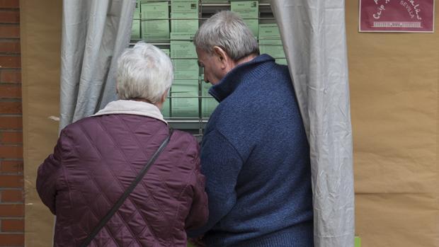 Dos votantes hoy en un colegio electoral de Sevilla