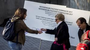 Una diputada de la CUP reparte papeletas en una campaña para un eventual referéndum de independencia en Cataluña