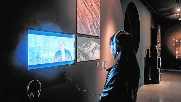 Una visitante observa un vídeo explicativo. A la izquierda, una recreación de Marte