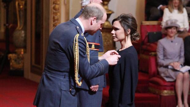 El príncipe Guillermo coloca la condecoración a Victoria Beckham