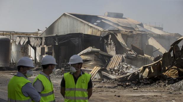 Tres operarios junto a la zona afectada por el incendio