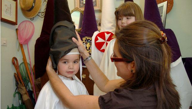 Un niño se prueba la túnica de nazareno / LÓPEZ RAMÍREZ