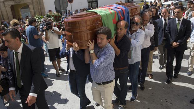 El féretro cubierto por la bandera del pueblo gitano y portado por familiares y amigos